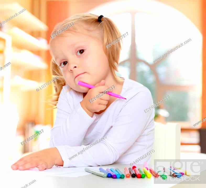 Stock Photo: Adorable little blonde girl with white t-shirts without a pattern, draws markers at the table on a white sheet of paper. The girl rested her head on the arm.