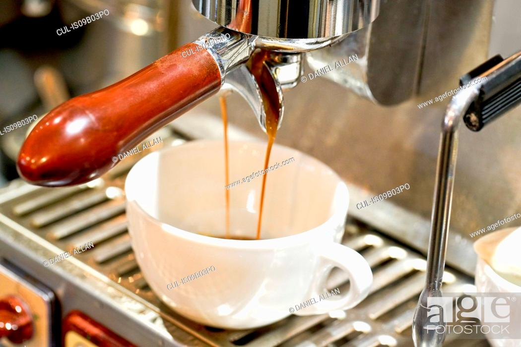 Stock Photo: Close up of coffee pouring into cup from coffee machine in cafe.
