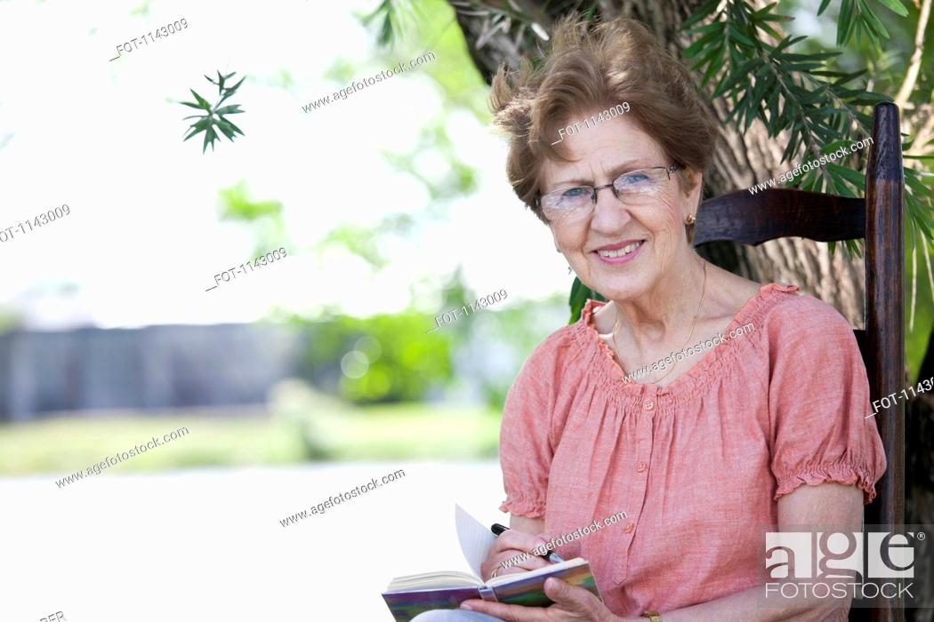 Stock Photo: Portrait of a senior woman writing in a book.