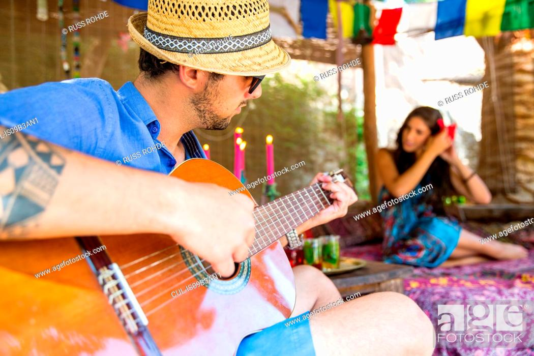 Imagen: Man playing guitar serenading woman.
