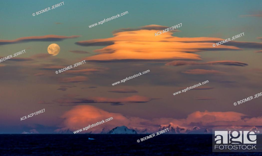Imagen: Dramatic Lenticular clouds share an evening sky with a full moon overlooking the Gerlache Strait, Antarctic Peninsula.
