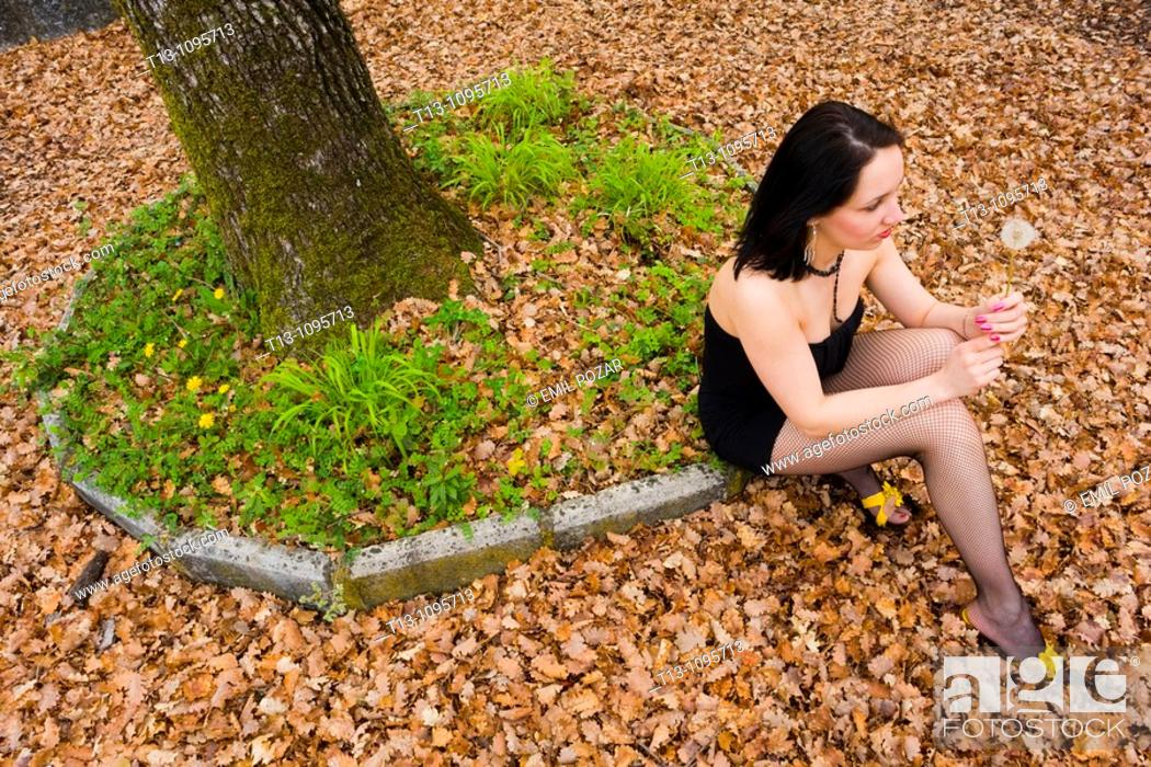 Stock Photo: Sexy woman is sitting in the park with a dandelion flower in hand.