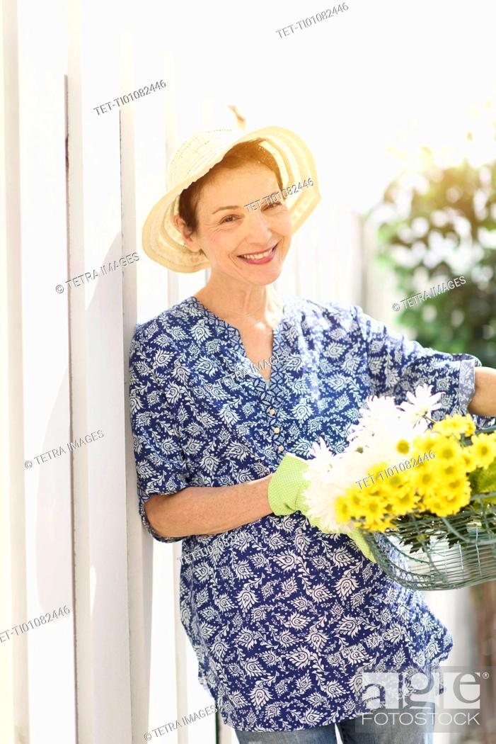 Stock Photo: Portrait of smiling senior woman with flowers.