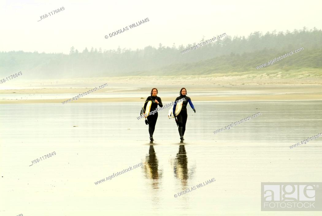 Stock Photo: two female surfers carry surfboards on the beach near Tofino, British Columbia, Canada.