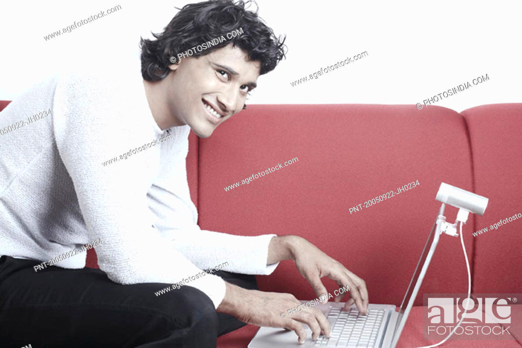 Stock Photo: Portrait of a young man sitting on a couch in front of a laptop.