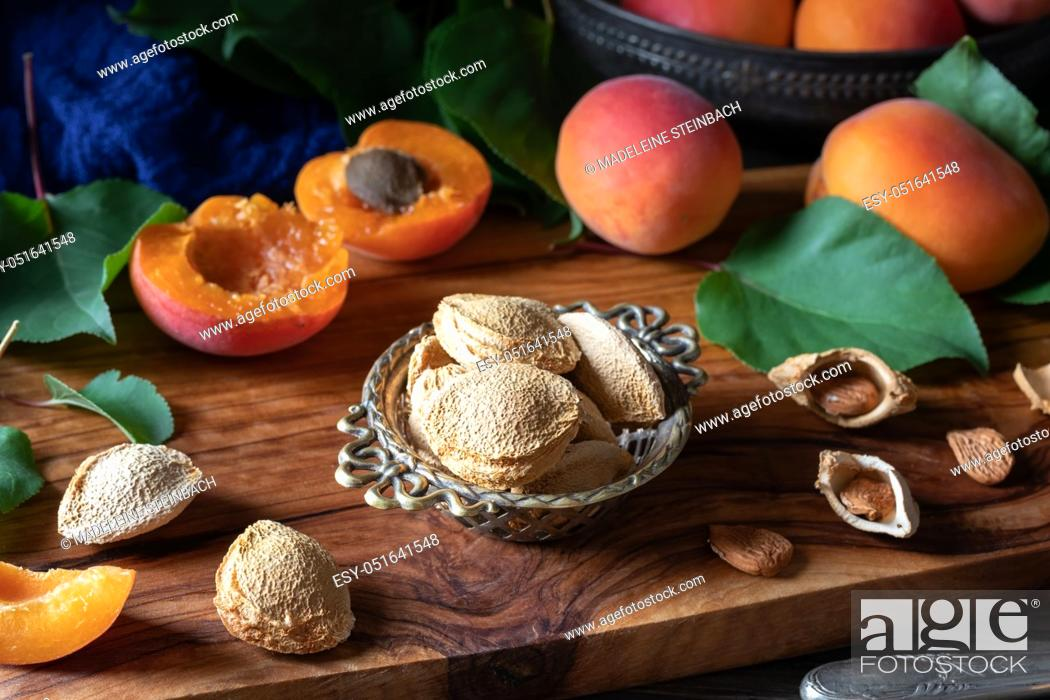 Stock Photo: Apricot kernels and fruit on a table.