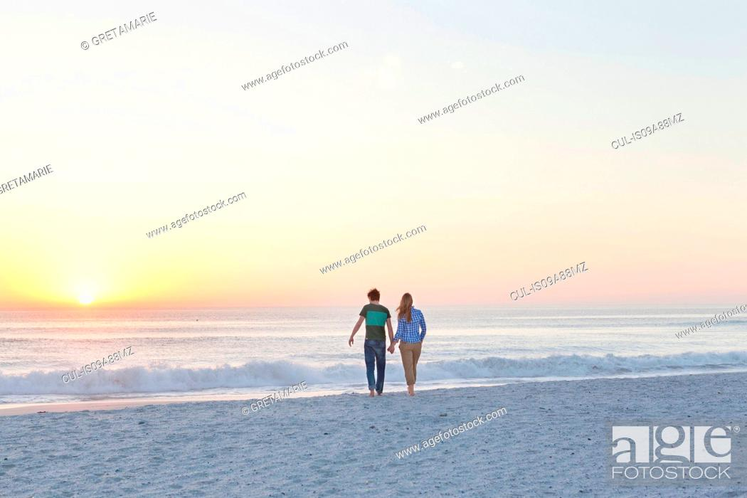 Stock Photo: Couple holding hands walking on beach.