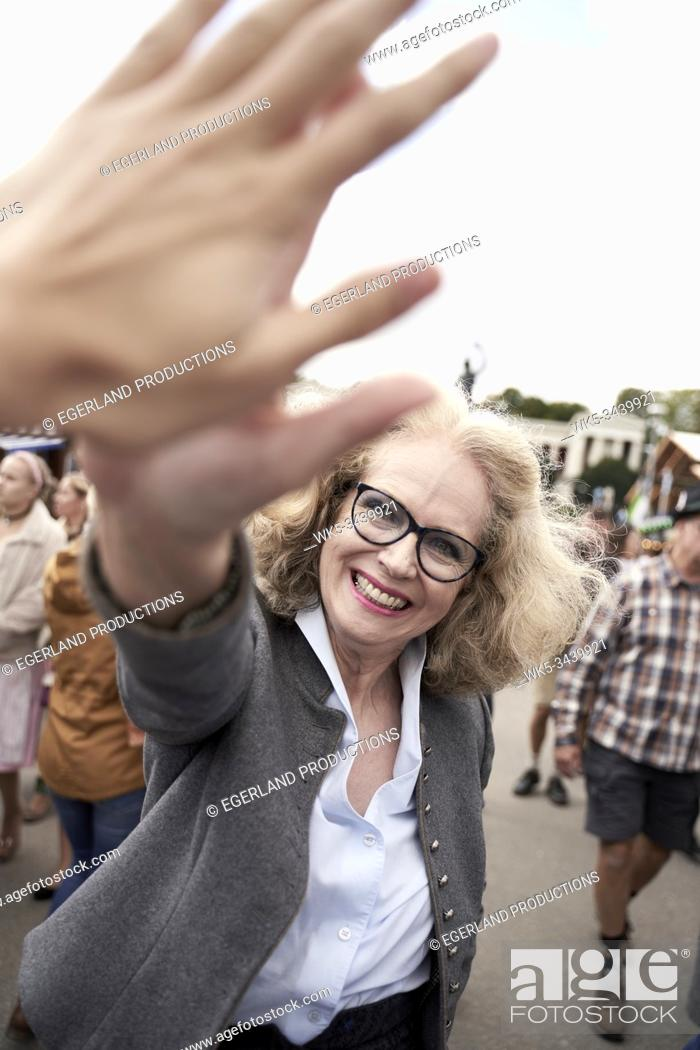 Stock Photo: Bavarian senior woman giving high five to counterpart at Oktoberfest in Munich, Germany.