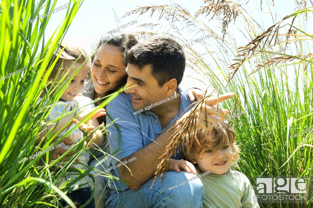 Stock Photo: Family crouching together in tall grass.