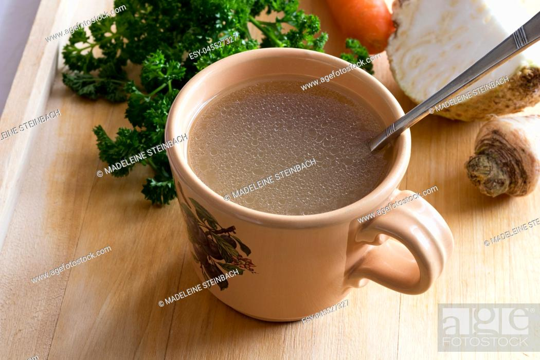 Stock Photo: Chicken stock in a vintage mug with a spoon, with parsley, carrot and celery root in the background.