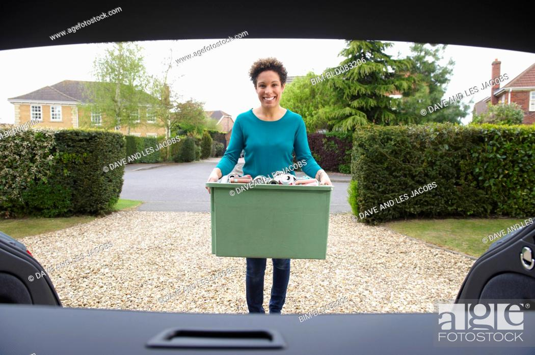 Stock Photo: Mixed race woman putting recycling in car.