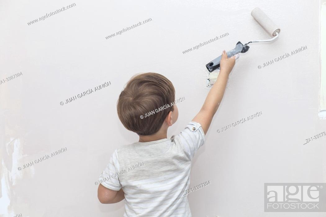 Imagen: 3 years cute little boy with paint roller in hand. Kids Helping House Chores concept.