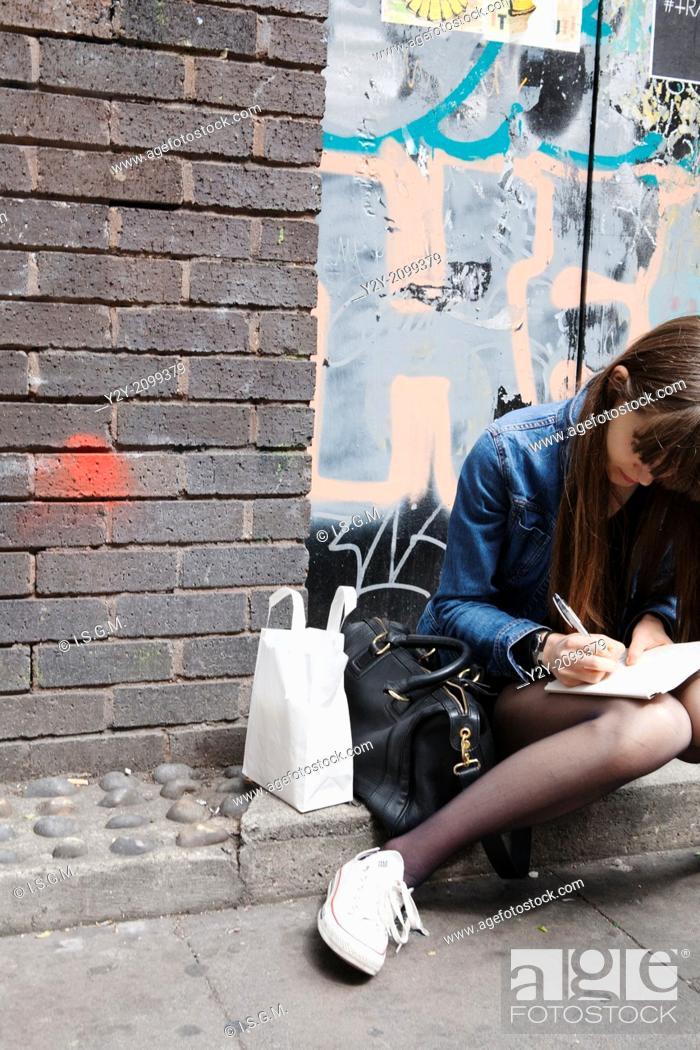 Stock Photo: girl writing in the street, London.