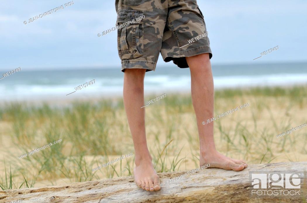 Stock Photo: Boy's legs near the sea.