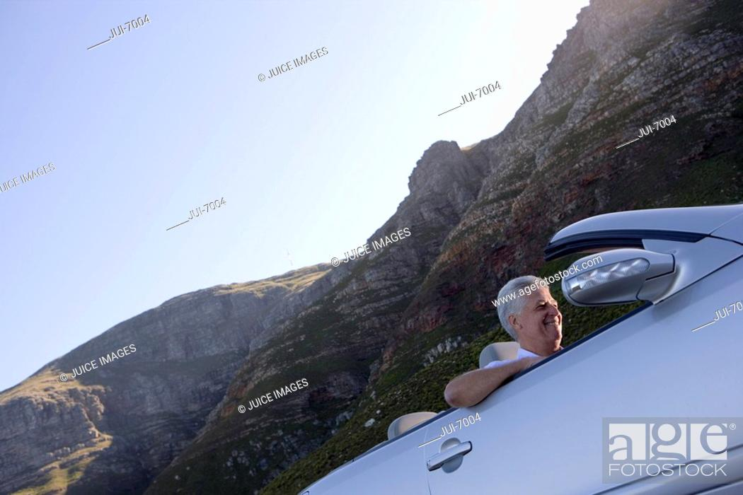 Stock Photo: South Africa, Western Cape, senior man driving silver convertible car along mountain road, smiling, side view, low angle view tilt.