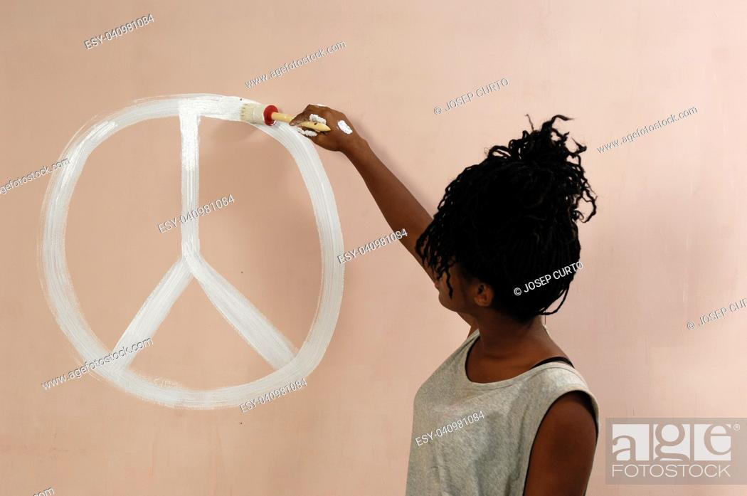 Stock Photo: teenager painting on a wall.