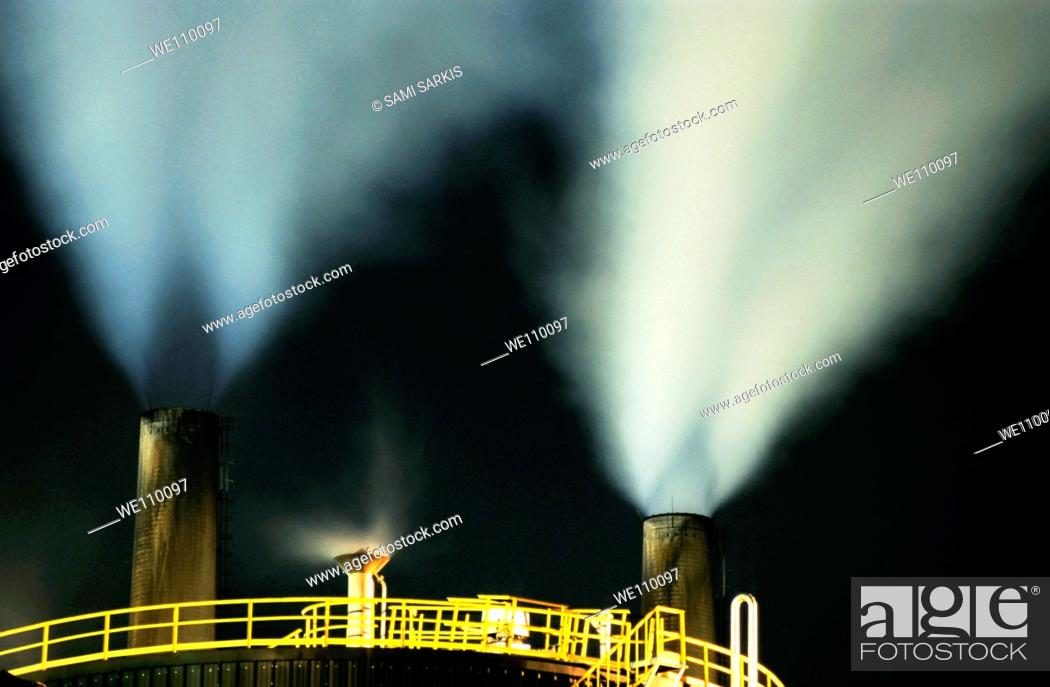 Stock Photo: Petroleum refinery chimneys at night, France.