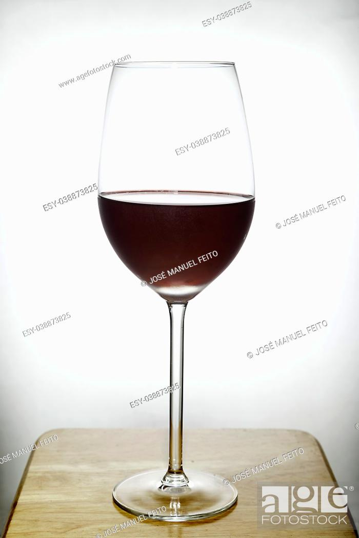 Stock Photo: glass of red wine on wood with white background.