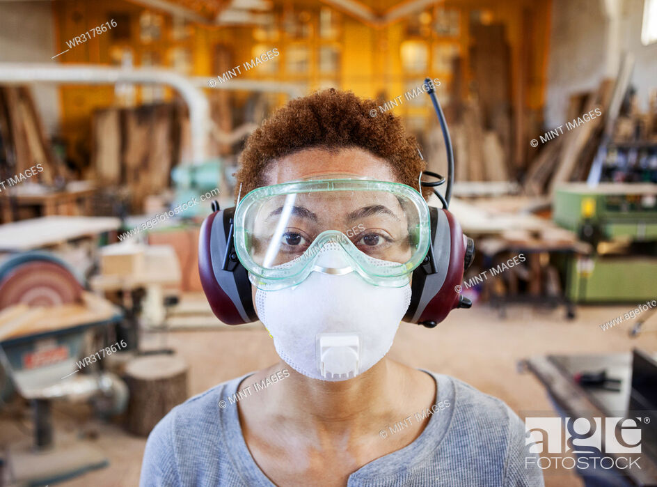 Stock Photo: Close up view of black woman factory worker wearing safety glasses and dust nose mask in a woodworking factory.