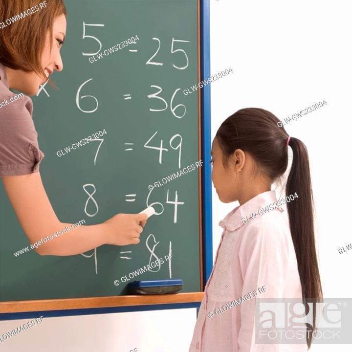Stock Photo: Side profile of a female teacher teaching a schoolgirl on a blackboard.