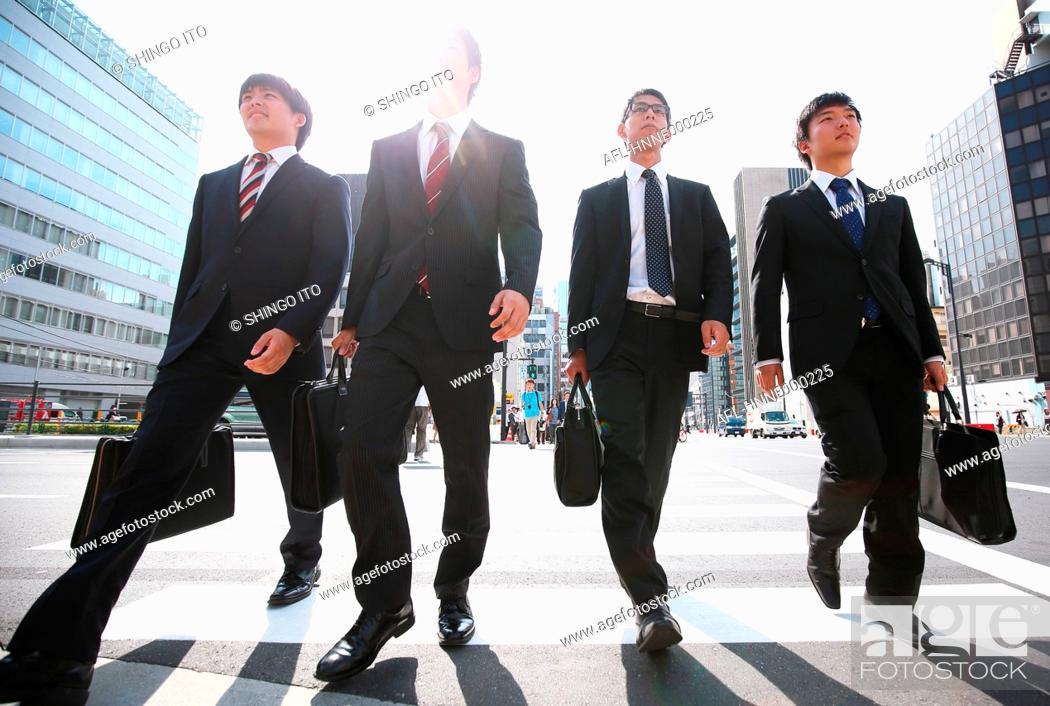 Stock Photo: Young Japanese businessmen walking.