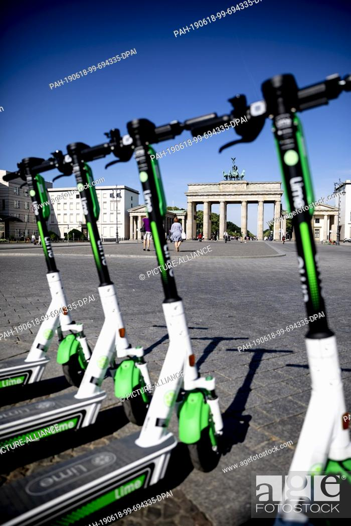 Imagen: 18 June 2019, Berlin: E- pedal scooters of the US-American company Lime are ready for rental in front of the Brandenburg Gate.