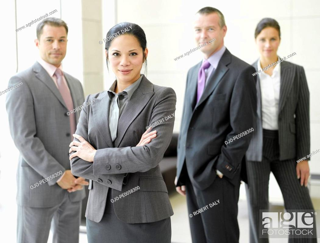 Stock Photo: Four businesspeople in office smiling.