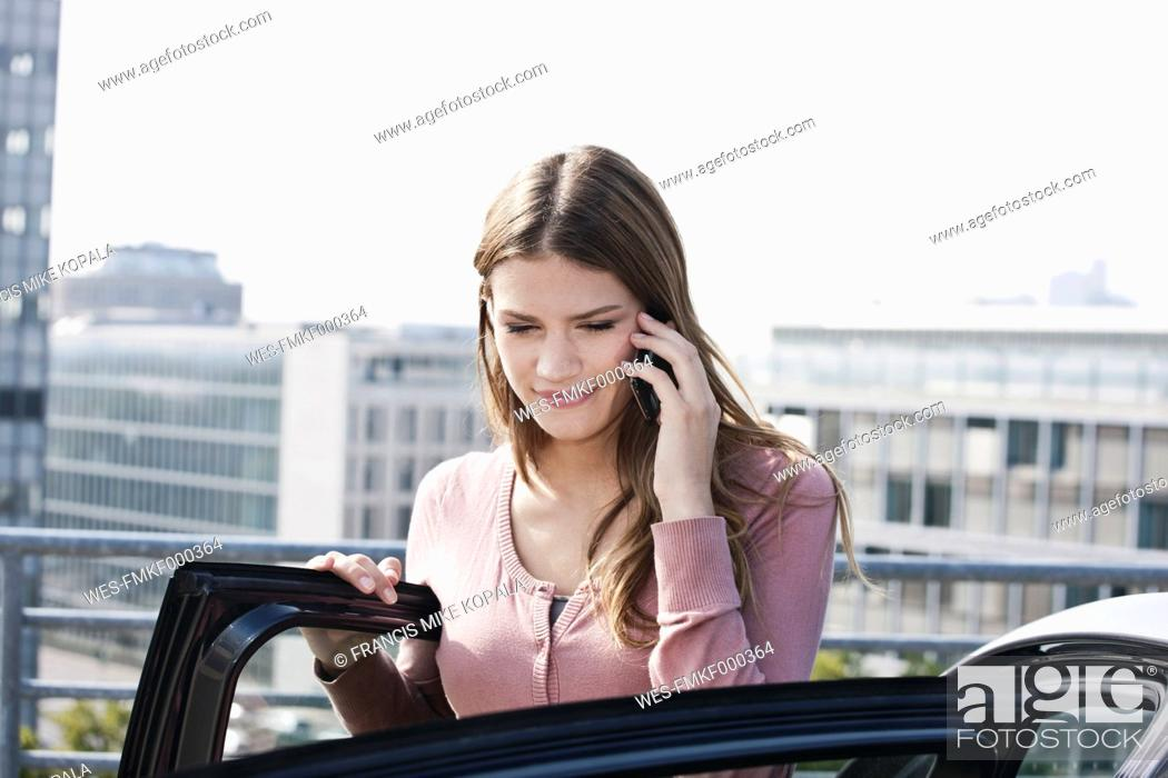 Stock Photo: Germany, Cologne, Young woman on phone near parking lot, smiling.