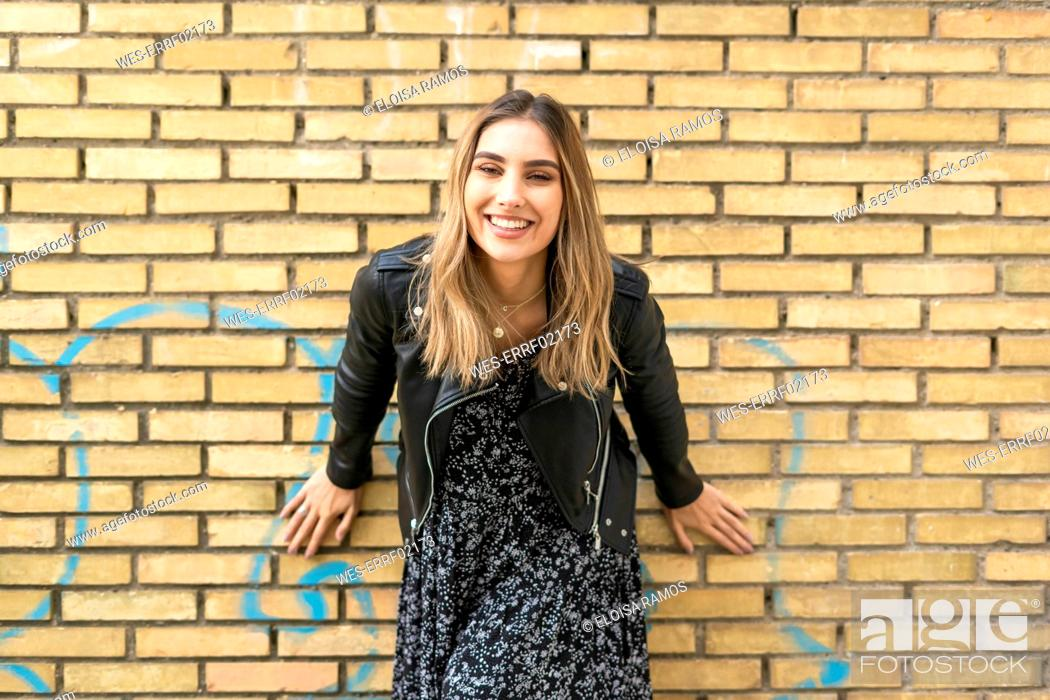 Stock Photo: Portrait of laughing young woman in front of brick wall.