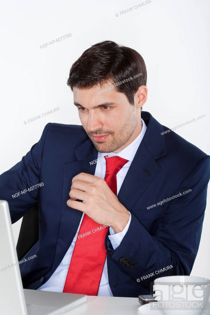 Stock Photo: young business executive in suit behind desk with laptop.