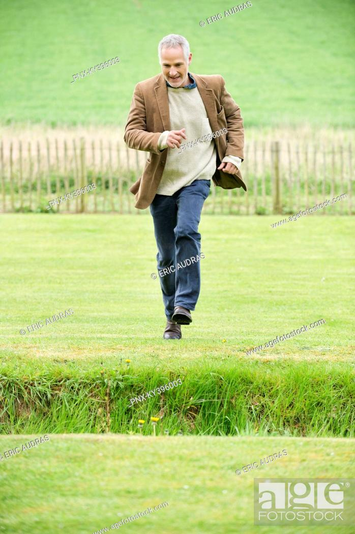 Stock Photo: Man running in a field.