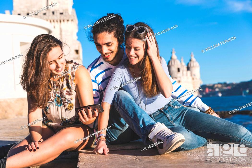 Imagen: Three friends, sitting on wall by sea, Belem Tower in background, Lisbon, Portugal.