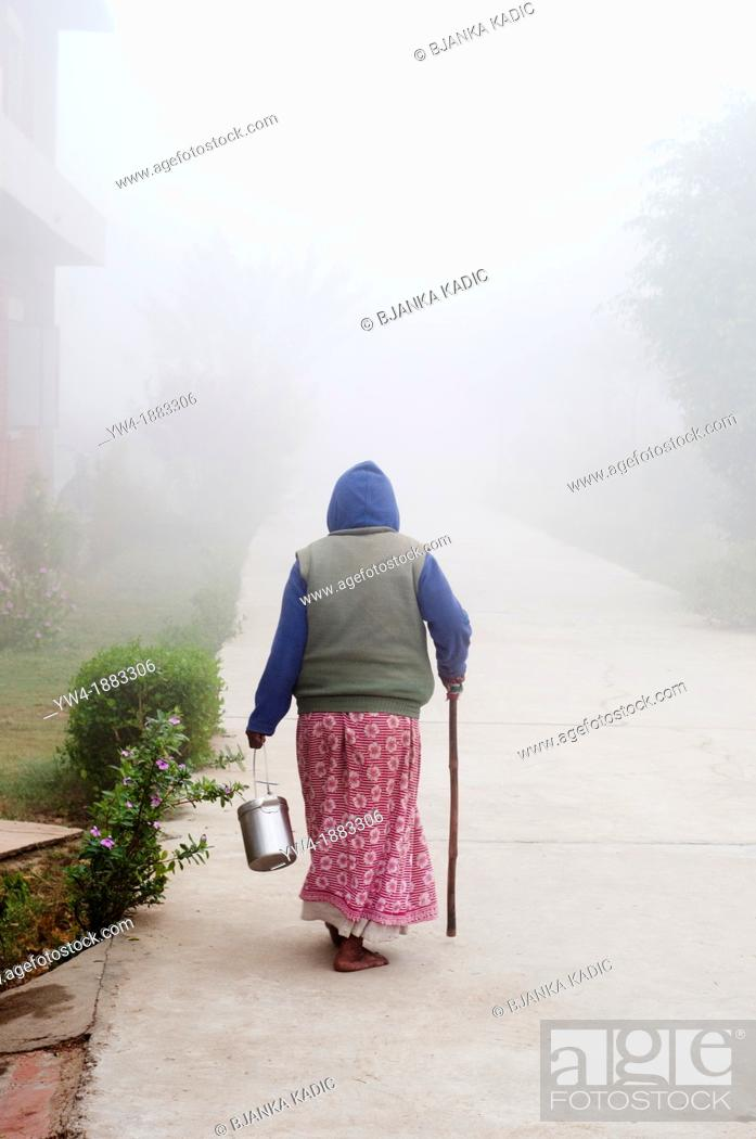 Stock Photo: Woman with a walking stick on a misty path, Ma Dham Ashram for widows, Vrindavan, Uttar Pradesh, India.