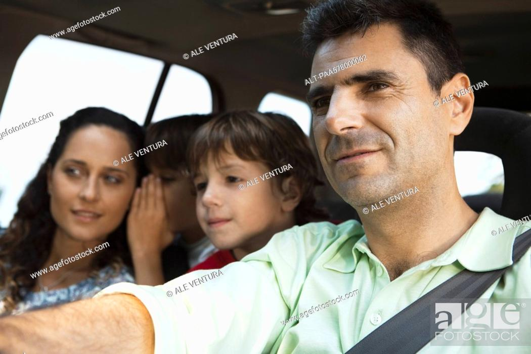 Stock Photo: Man driving with his family.