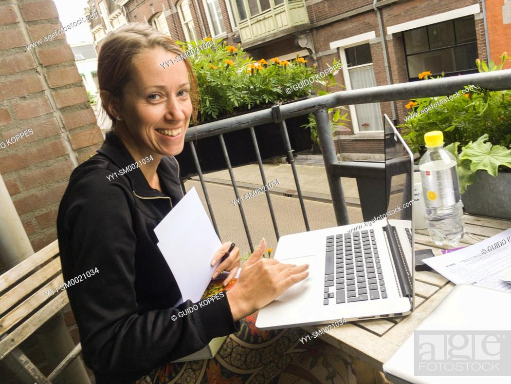 Stock Photo: Tilburg, Netherlands. Adult blonde woman, working on her notebook computer while sitting at a balcony table, cooperating with a colleague.