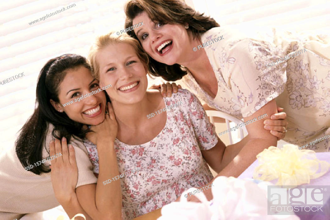 Stock Photo: Portrait of three young women smiling at a baby shower.