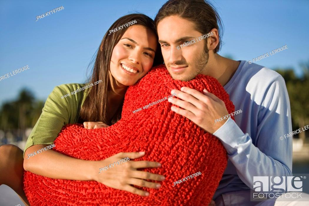 Stock Photo: Portrait of a couple hugging a heart shaped cushion.