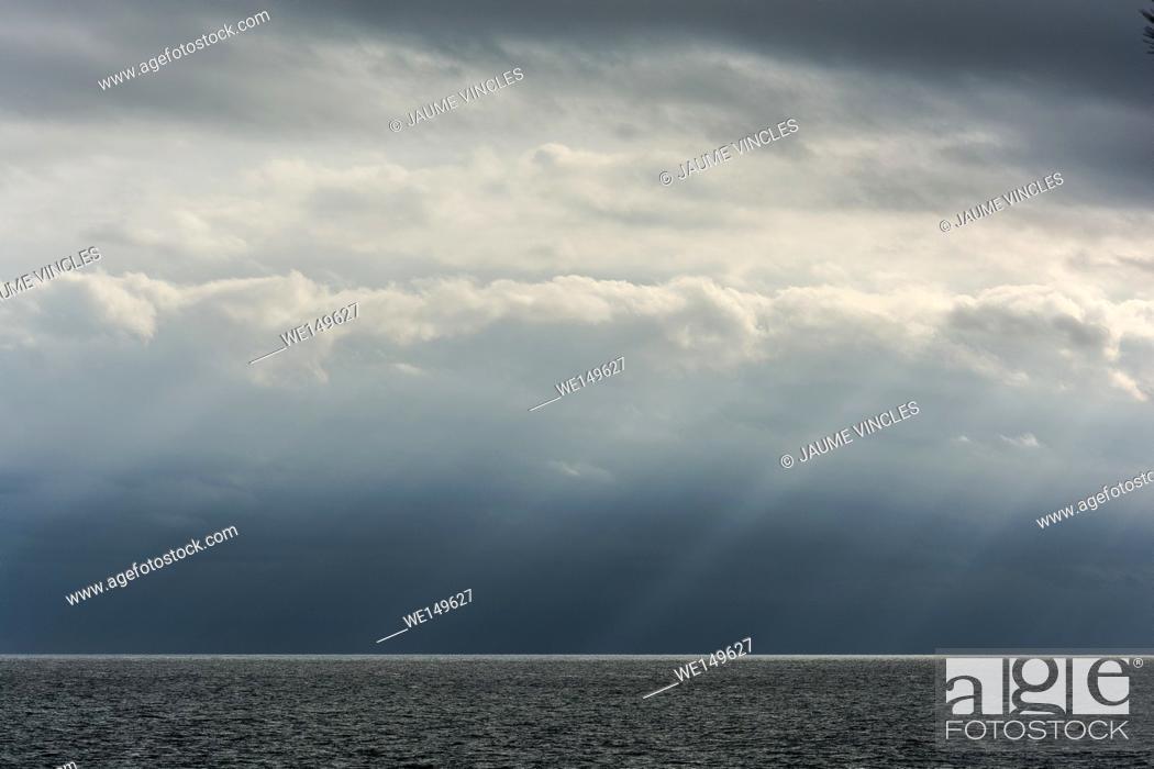 Photo de stock: The sky seems to cry tears of light, divine scenery on the coast of Barcelona.