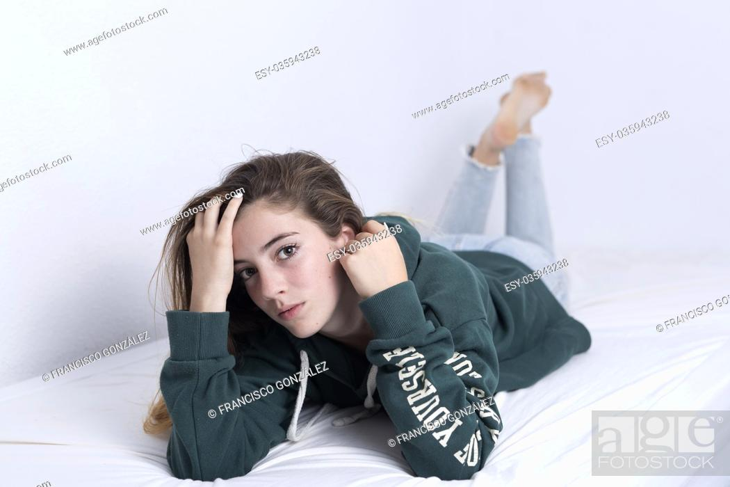 Stock Photo: 15-year-old adolescent lying on her bed. Studio soft light.