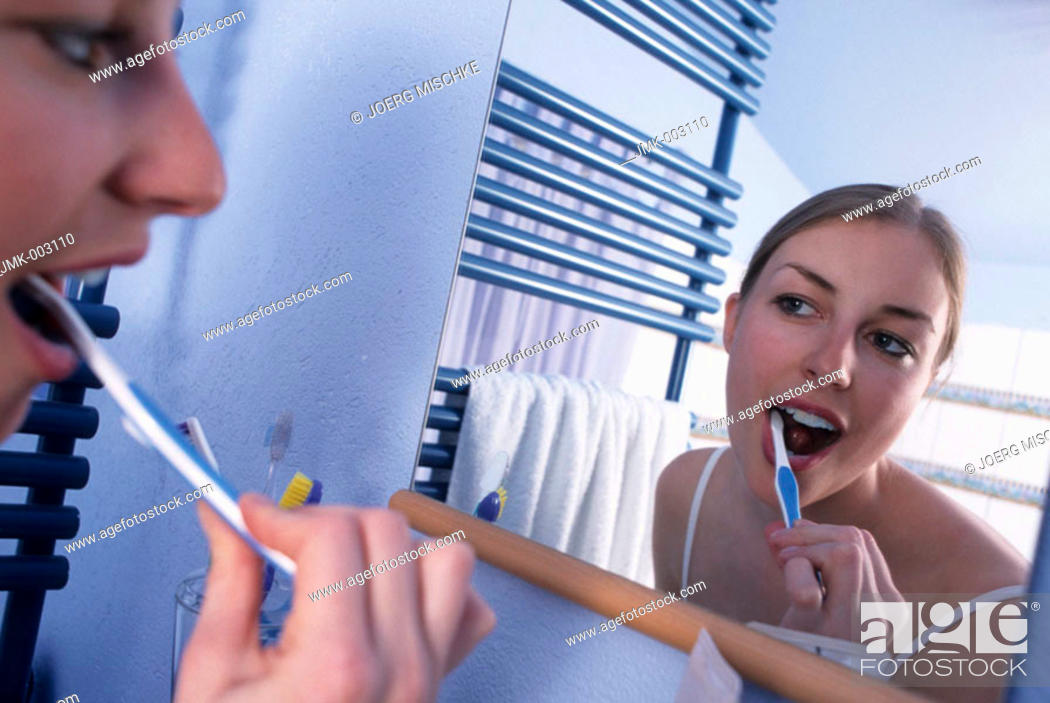 Stock Photo: A young woman, 20-25 25-30 years old, in the bathroom, brushing her teeth in front of a mirror.