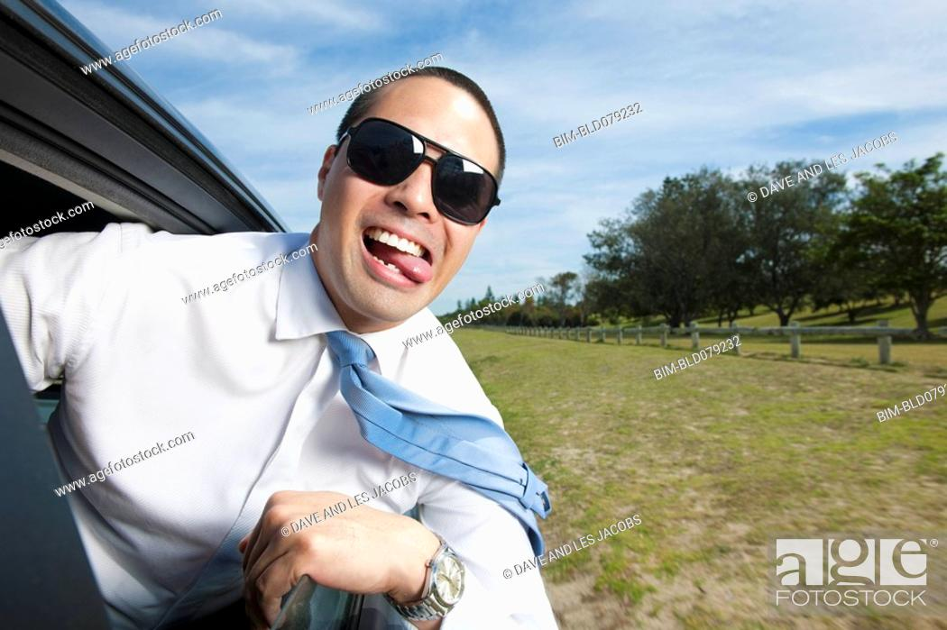 Stock Photo: Asian businessman riding in car with head out window.
