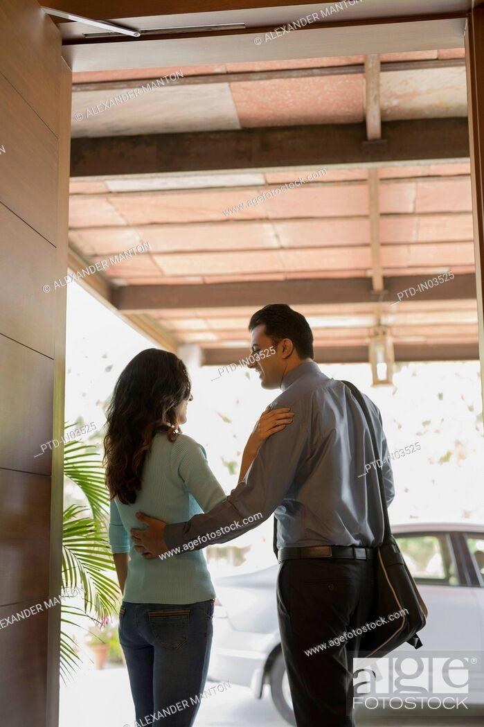 Stock Photo: India, Woman saying goodbye to man at front door.