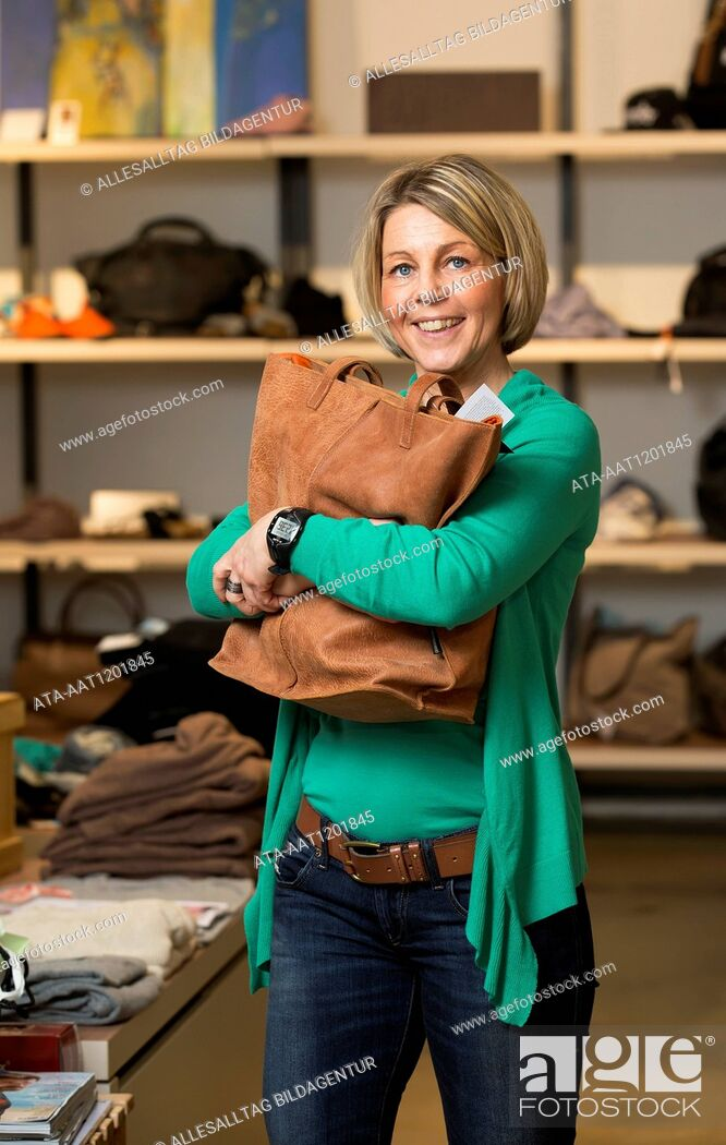 Stock Photo: Happy woman with a leather handbag in a boutique.