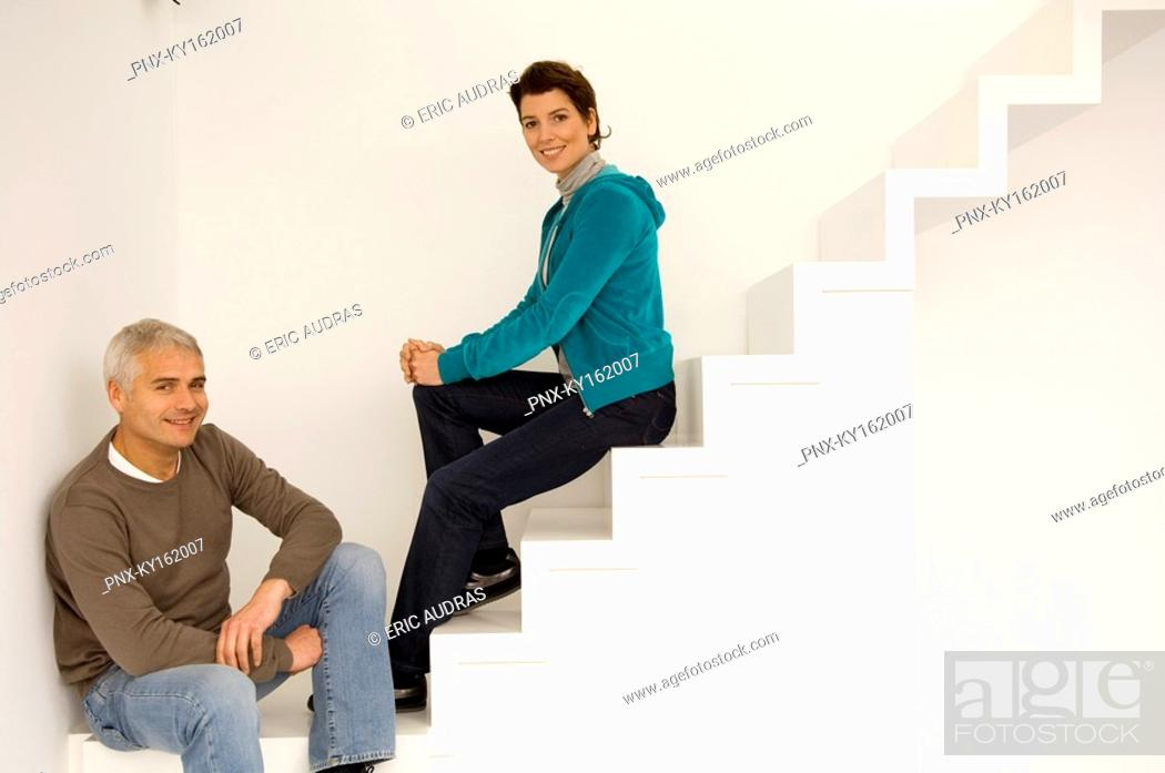 Stock Photo: Portrait of a mature man and a mid adult woman sitting on a staircase.