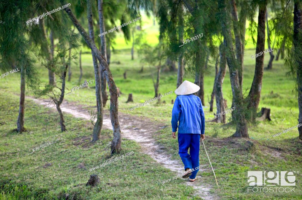 Stock Photo: Vietnamese man walking in the woods near Hoi An.