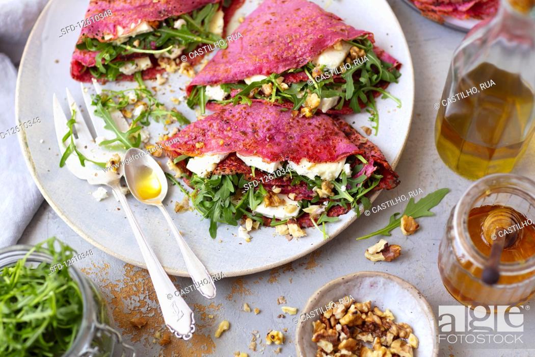 Stock Photo: Crepes (with beetroot juice) with arugula nad feta.