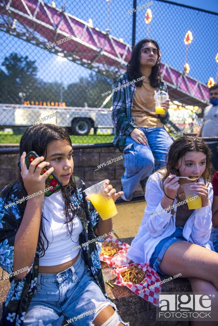 Photo de stock: A happy, diverse group of girl friends hang out at the county fair on a summer night. A hispanic girl talk on her cellphone while the others eat and drink and.