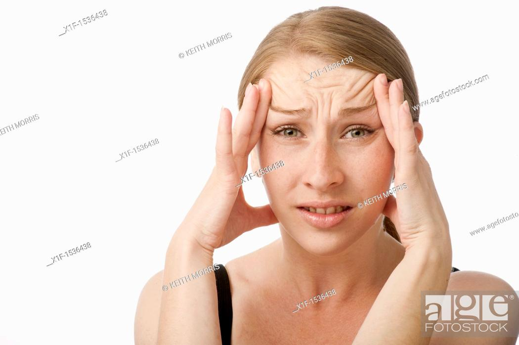 Stock Photo: a young caucasian woman with a headache rubbing her forehead to relieve the pain, UK.