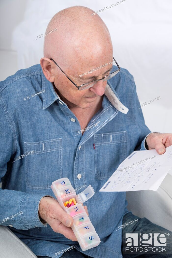 Stock Photo: Senior man holding a prescription and a weekly pill organiser.