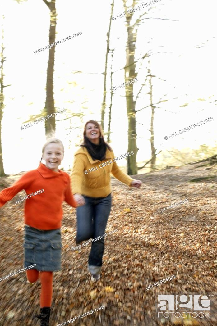 Stock Photo: Mother and daughter running in woods.